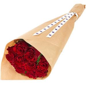 Bukett med röda rosor, fint inslagna i omslagspapper. Skicka rosorna med ett blombud från Euroflorist och överraska din vän!