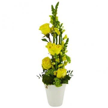 Hög dekoration med gula blommor och grönt. Finns att beställa hos Florister i Sverige.