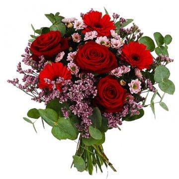 Bukett med blandade blommor i varma färger, främst rött och rosa. Blommorna finns hos Florister i Sverige.