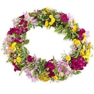 Vacker blomsterkrans till håret. Blandade sommarblommor, här i lila, rosa, gult och grönt. Beställ sommarkransen i Euroflorists webshop!