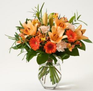 Höstbukett i orange färgtoner. Blommor: liljor, germini, nejlikor och alstroemeria. Buketten finns hos Intgerflora.